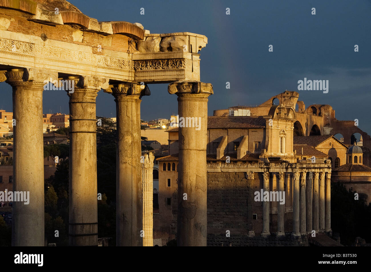 columns of Temple of Saturn with Saint Luca and Martina Church at the ancient Roman forum site, Rome Italy - Stock Image
