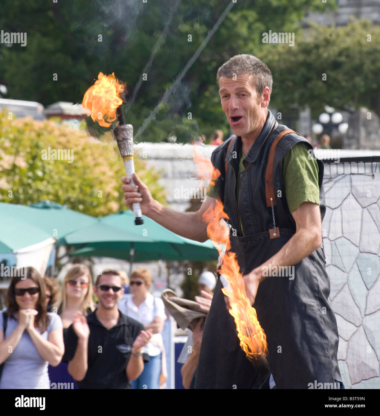 street artist on stilts with fire sticks at harbourfront, Victoria, Vancouver Island, British Columbia, Canada - Stock Image