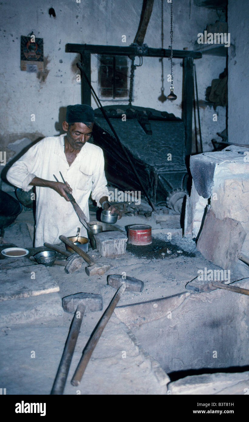 India, Gujarat, Kutch. A blacksmith tends his forge with a huge hand-pulled bellows in the village of Zura. Zura - Stock Image