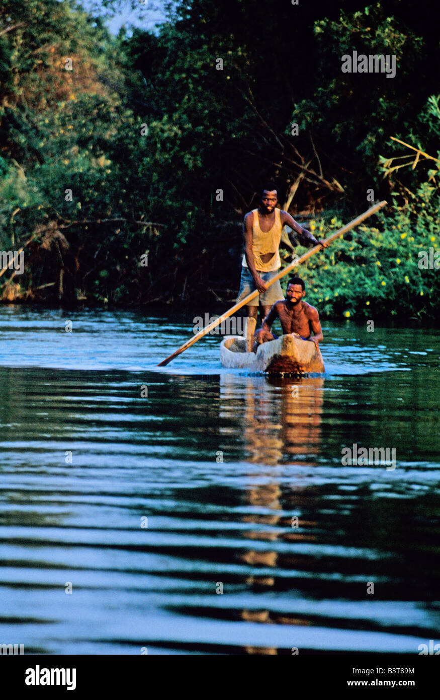 Africa, Bostwana. Two fishermen in dugout canoe paddle in river. - Stock Image