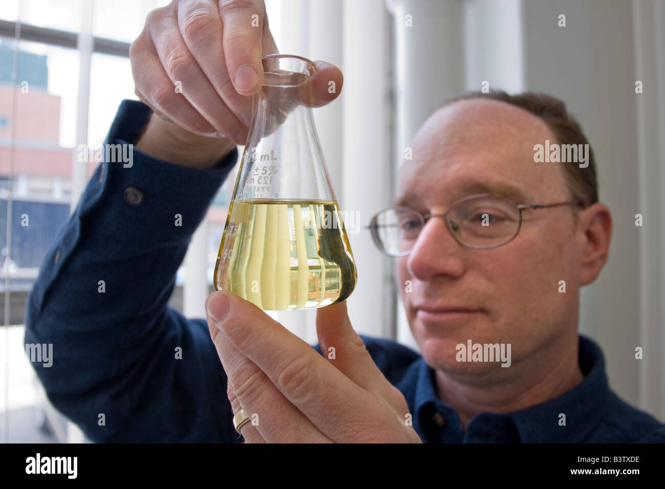 A scientist with a beaker of Bio-diesel made from cooking oil - Stock Image