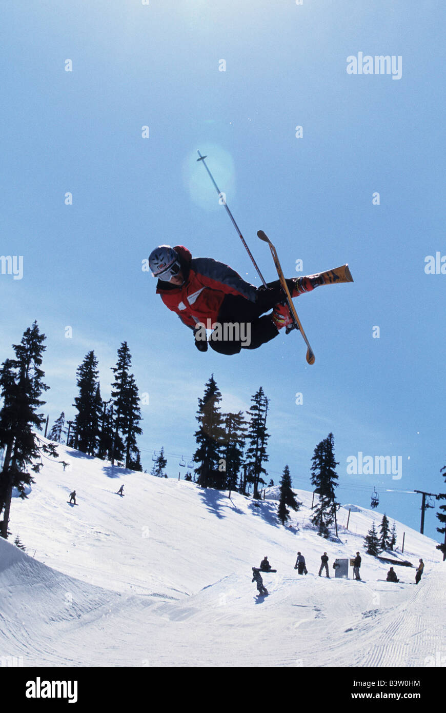 A skier dose a mute grab in the half pipe - Stock Image