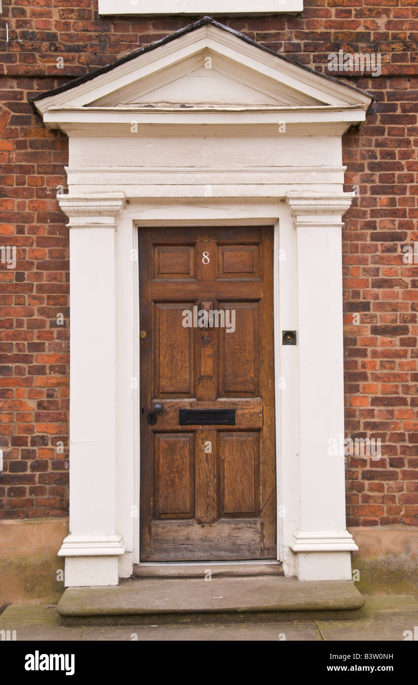 Brown Wooden Front Door With White Frame And Pediment On Townhouse