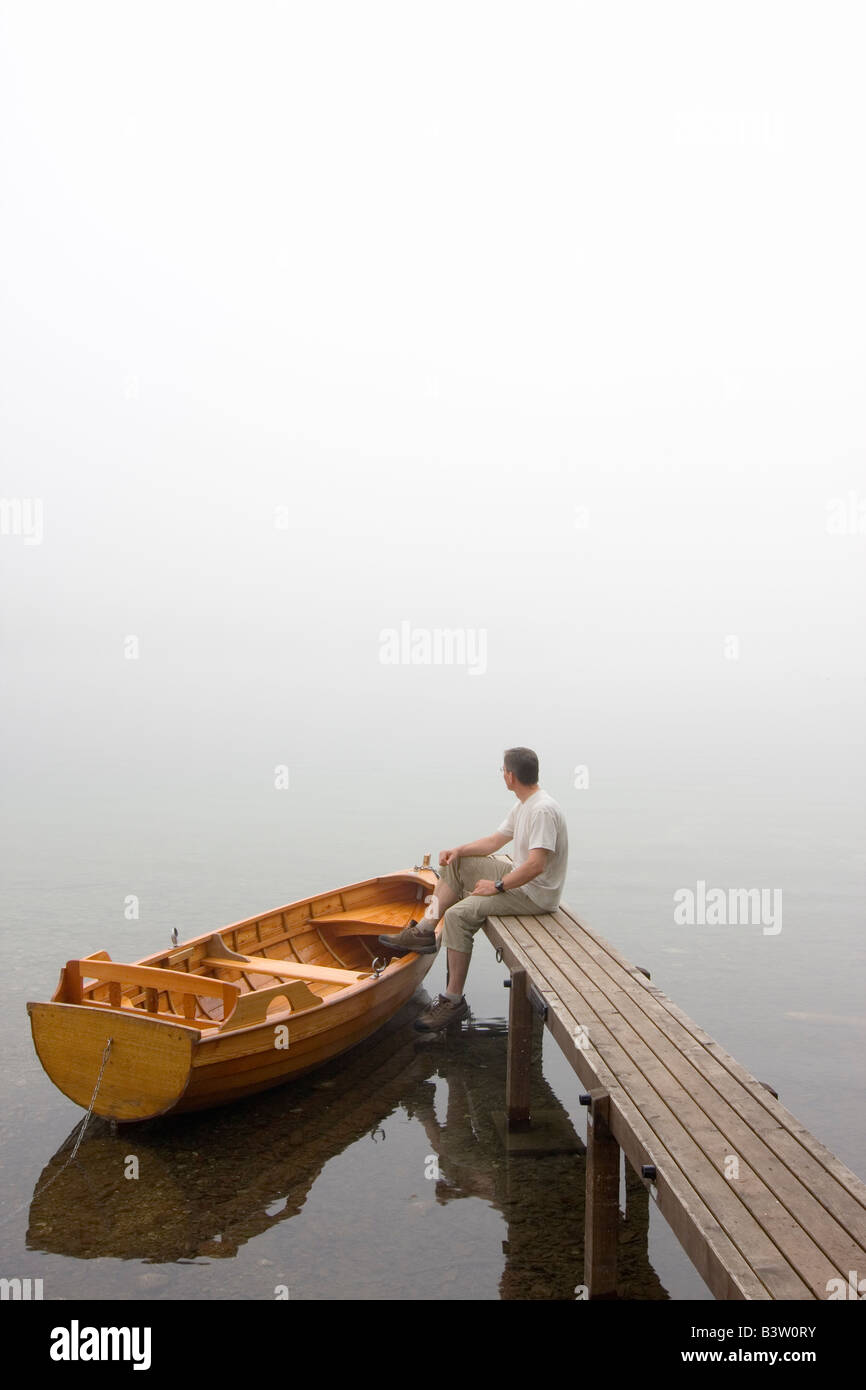Man sitting on a landing stage at a misty morning in fall Stock Photo