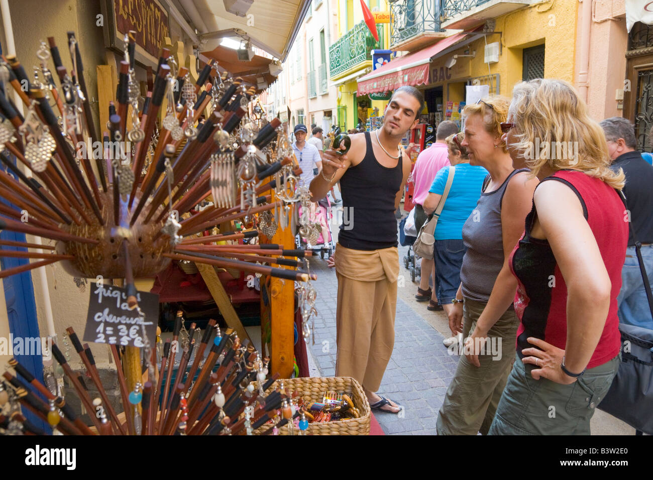 An art handicraft dealer in an old town street offers costume jewellery to two female tourists in Collioure / Southern - Stock Image
