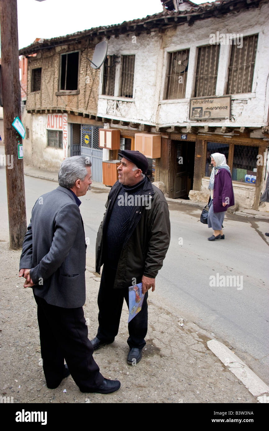Two man chat on a street in front of old Ottoman house in Prizren, Kosovo. Prizren is Kosovo's historical and - Stock Image