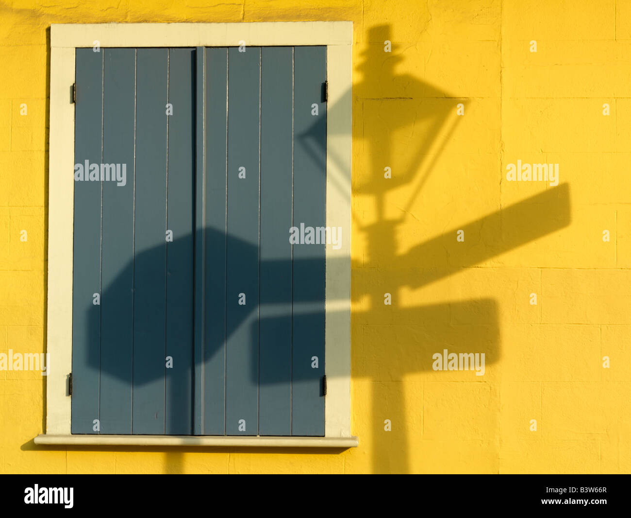 USA,Louisiana,New Orleans,French Quarter,shadow of French Quarter lamp post on a yellow wall - Stock Image