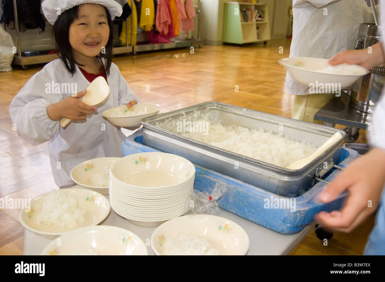 Japanese elementary school student serves lunch to her classmates - Stock Image