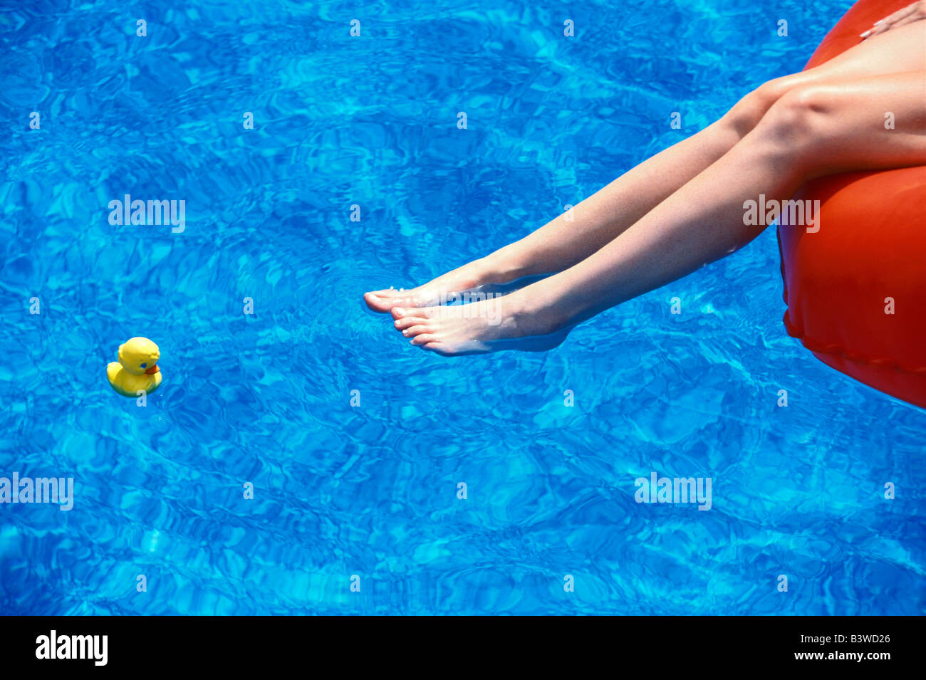 Woman s legs and her rubber ducky in a swimming pool - Stock Image