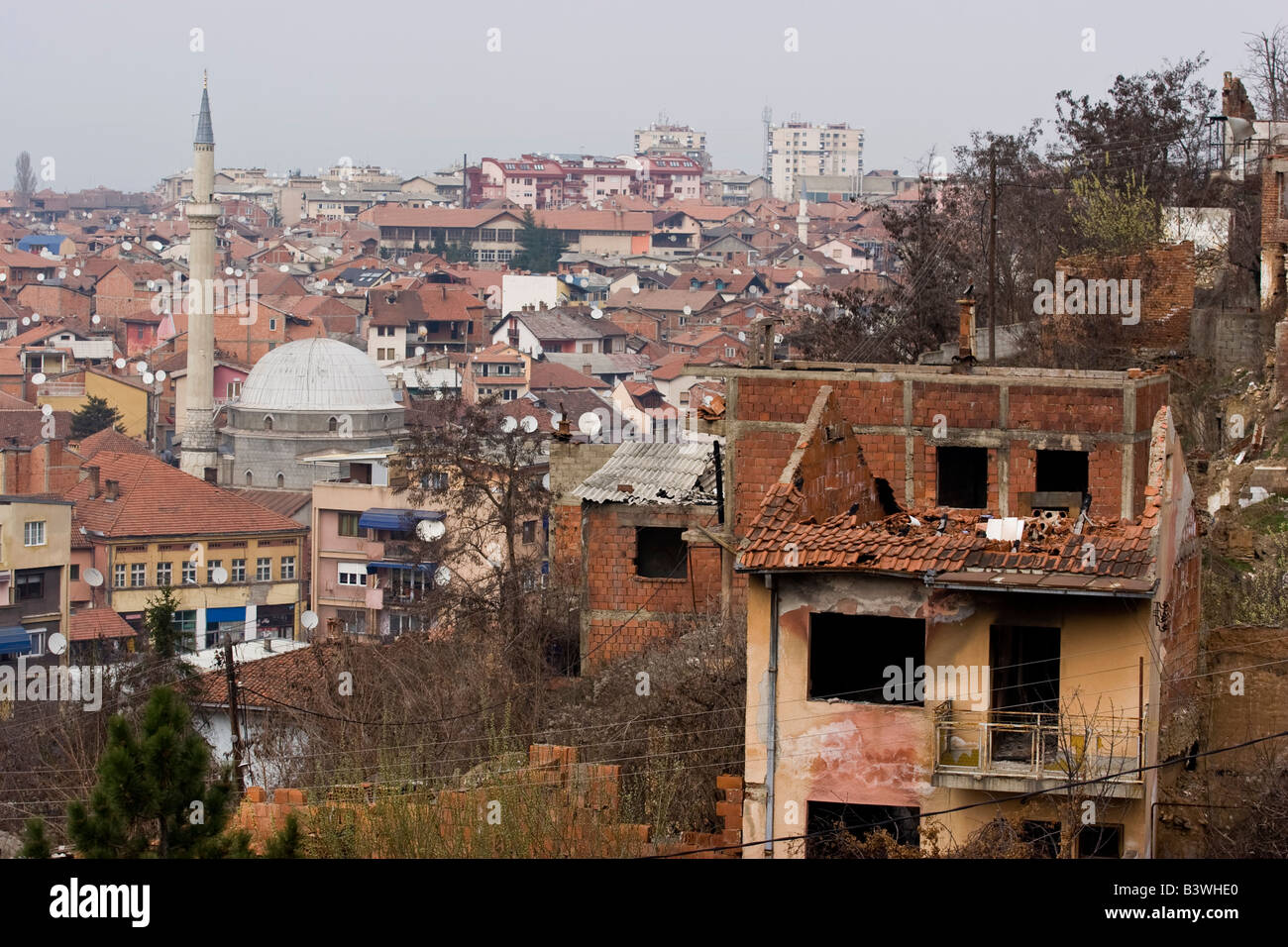 A burned out in 2004 riots shell of Serb house with a mosque in background, Prizren, Kosovo. - Stock Image