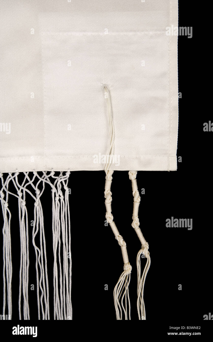 Fringes called tzitzit are sewn to the corners of a Jewish prayer shawl called a tallit isolated on a black background - Stock Image