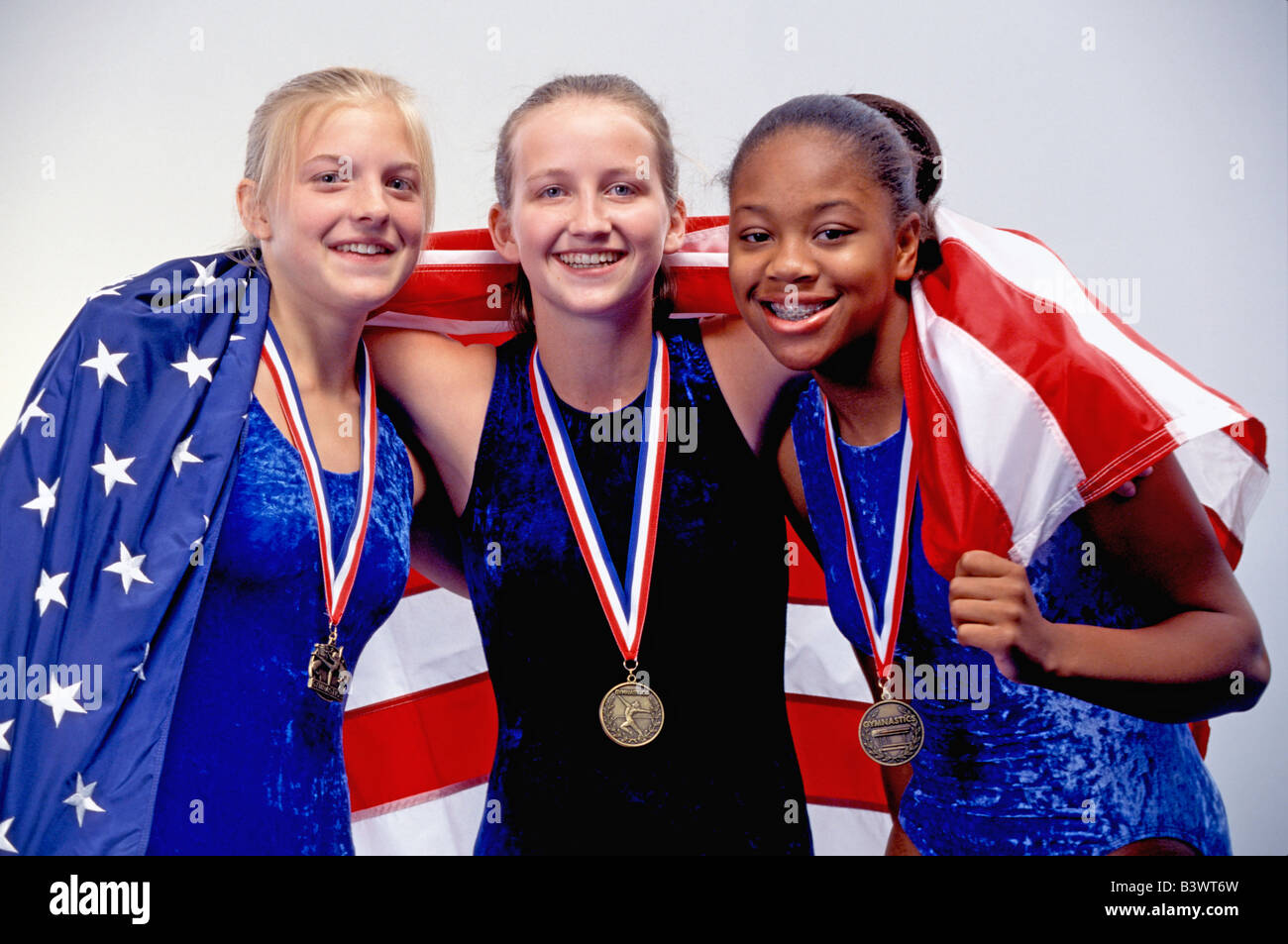 Winning Female gymnasts drape themselves in American flag - Stock Image