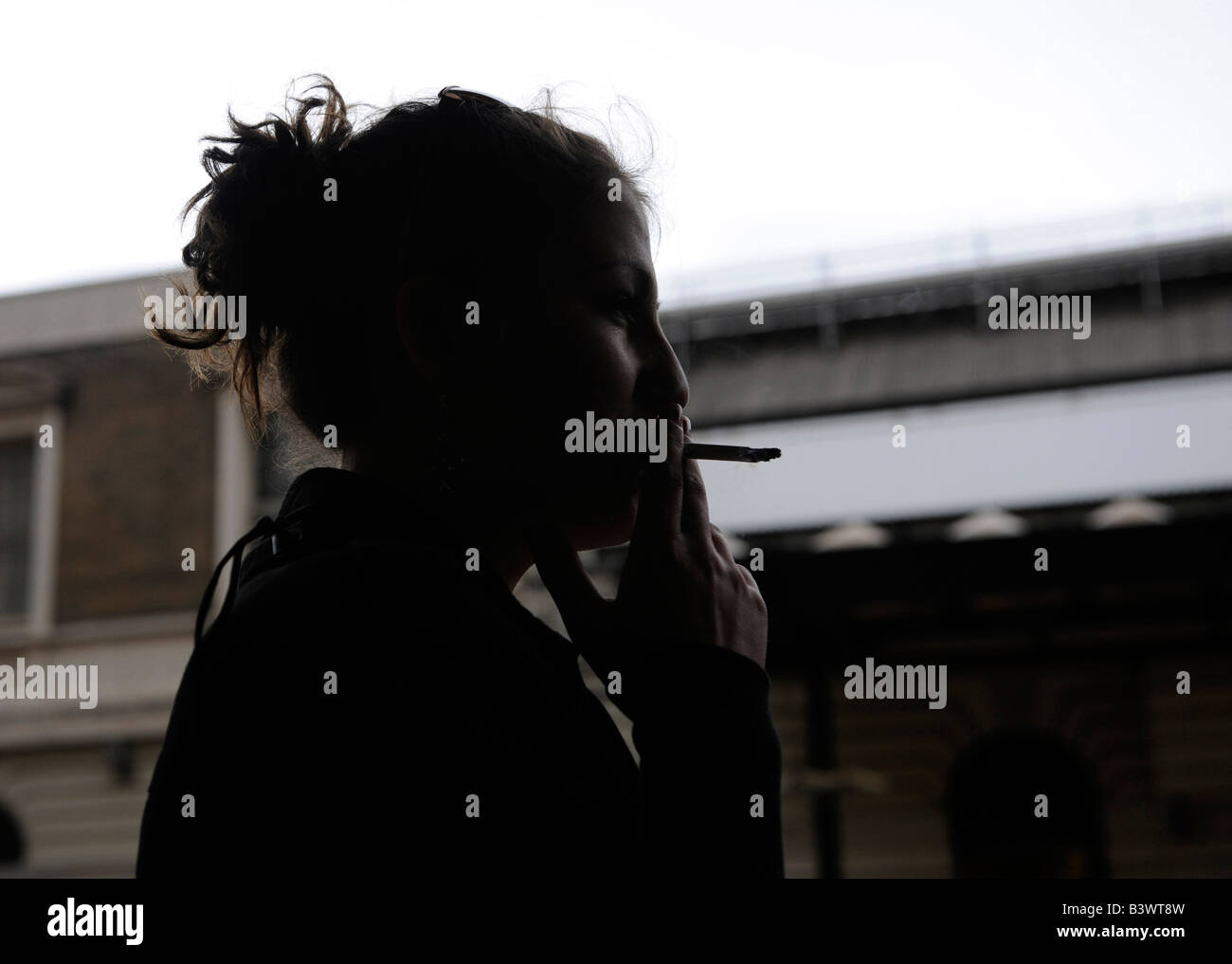 Side profile of a young woman smoking a cigarette, London, England - Stock Image