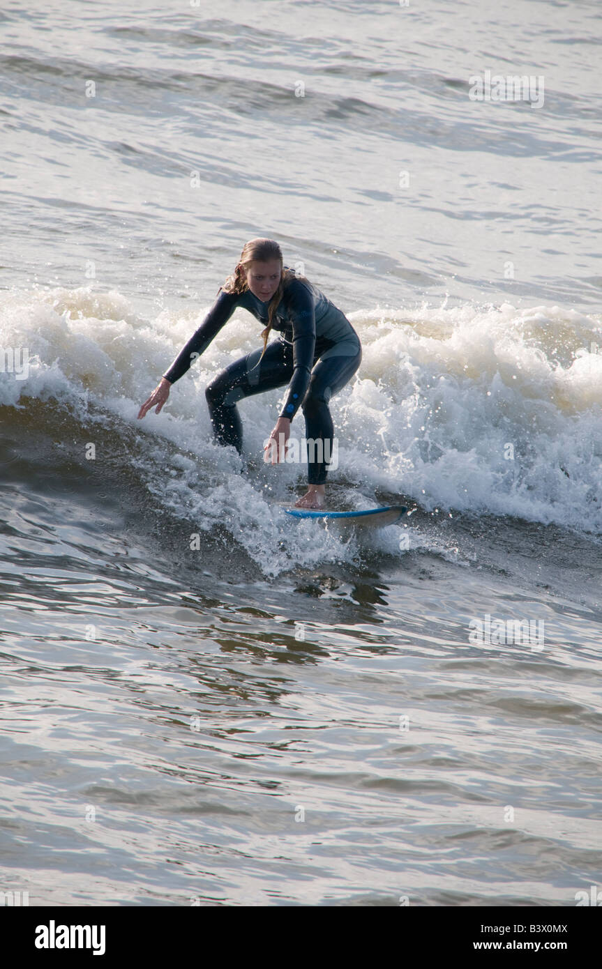 Young blonde teenage girl wearing wetsuit on surfboard surfing on the waves off Aberystwyth Wales UK, summer afternoon - Stock Image