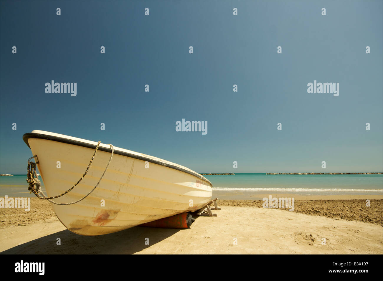 A white rowing boat sits on the beach at Grottamare in the Italian region of Le Marche - Stock Image