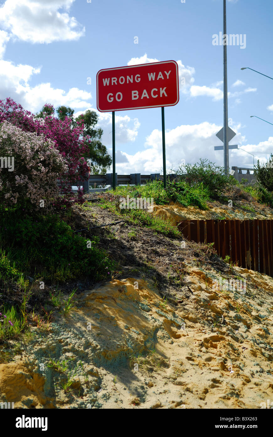 Red and white 'Wrong Way, Go Back' sign - Stock Image