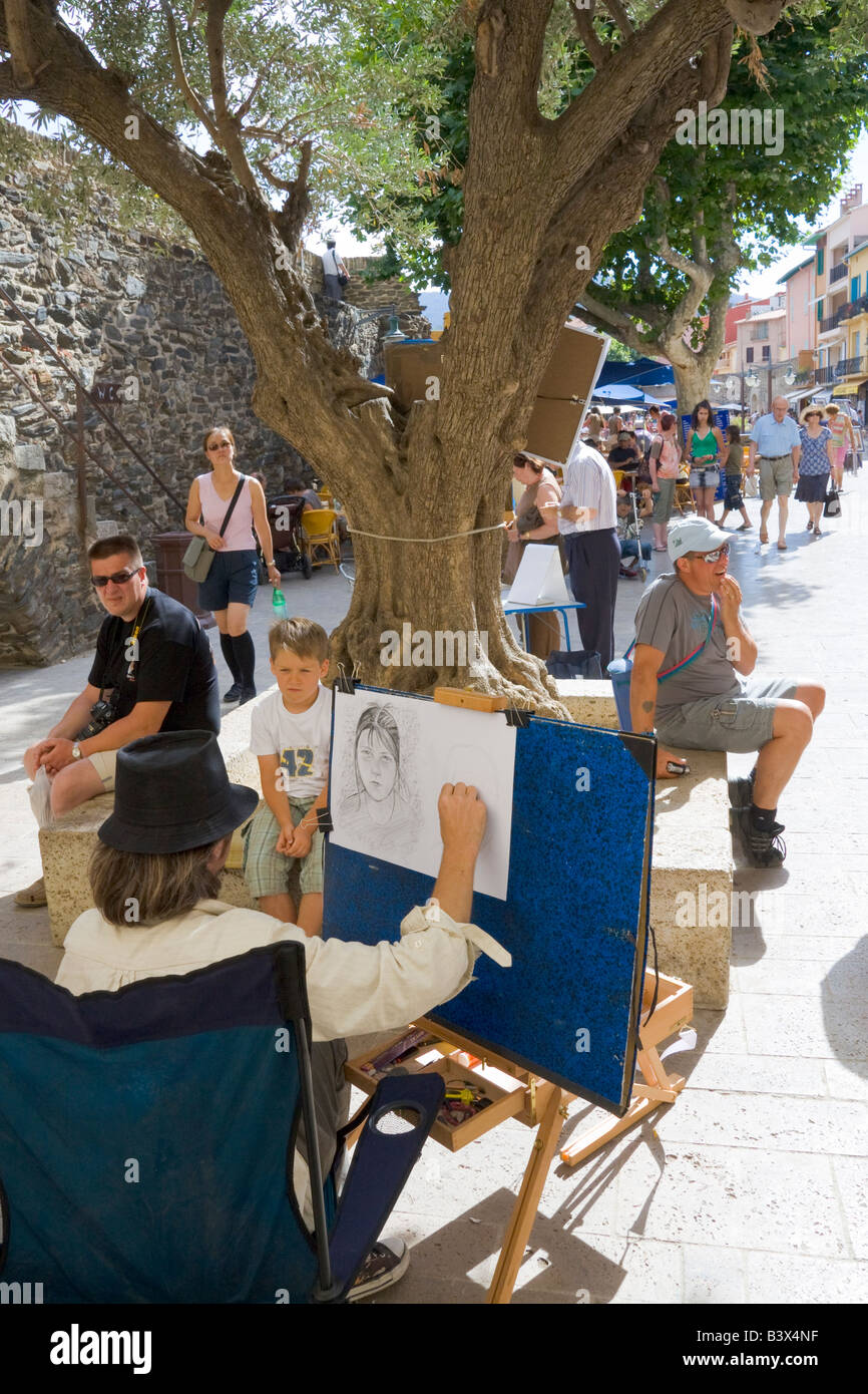 A painter sits with his easel on the roadside, drawing a portrait of a child in Collioure / Southern France - Stock Image