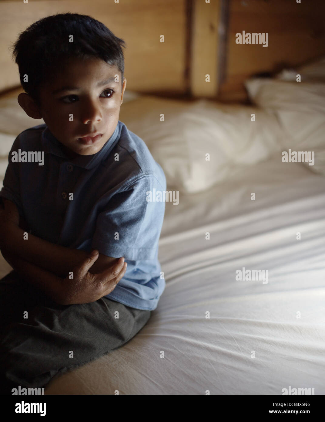 A five year old boy wearing a blue top and grey trousers sits on the edge a bed looking sad, lonely, abandoned and - Stock Image