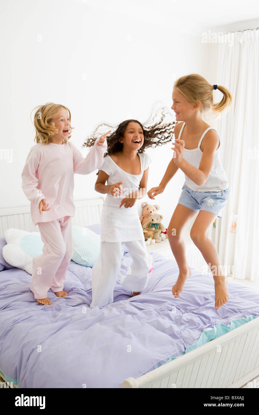 Three Young Girls Jumping On A Bed In Their Pajamas - Stock Image