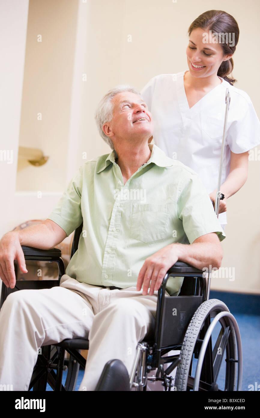 Nurse Pushing Man In Wheelchair - Stock Image