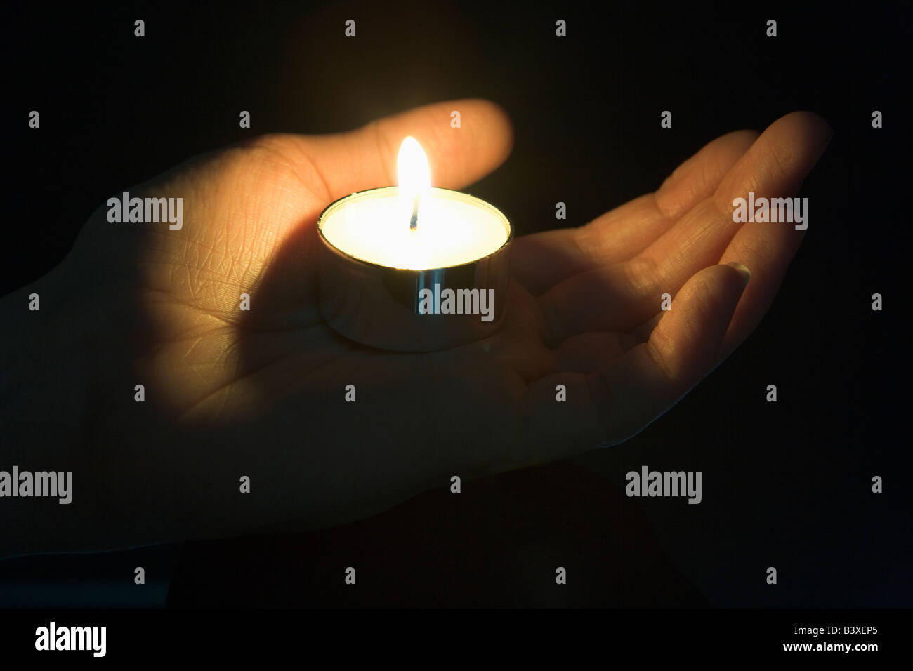 Close-Up Of Candle In The Palm Of A Persons Hand - Stock Image