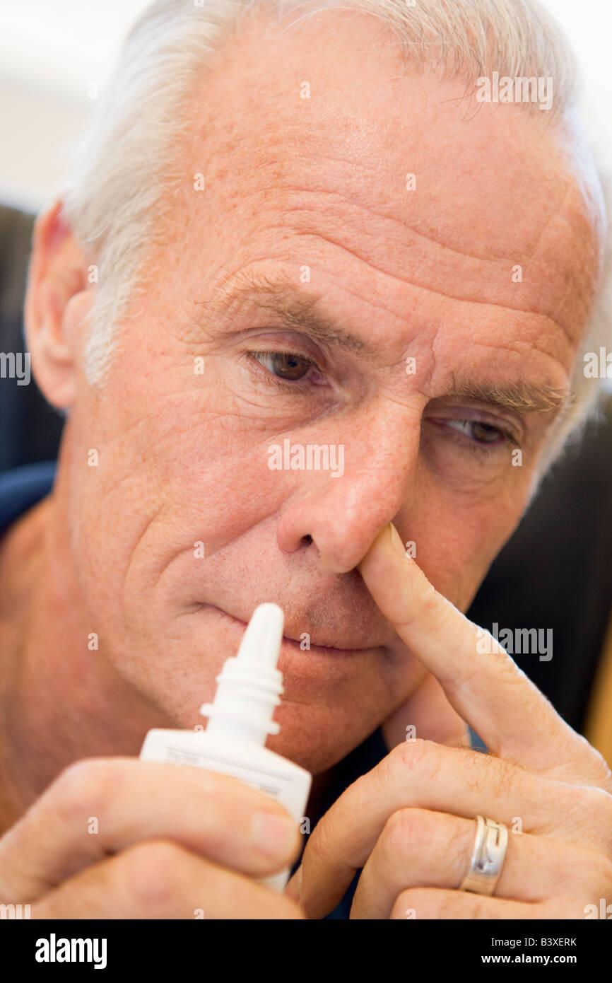 Senior Man Using Nasal Spray Stock Photo