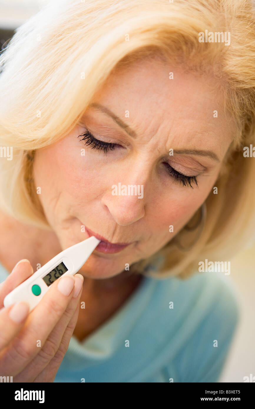 Woman Taking Her Temperature With Thermometer - Stock Image