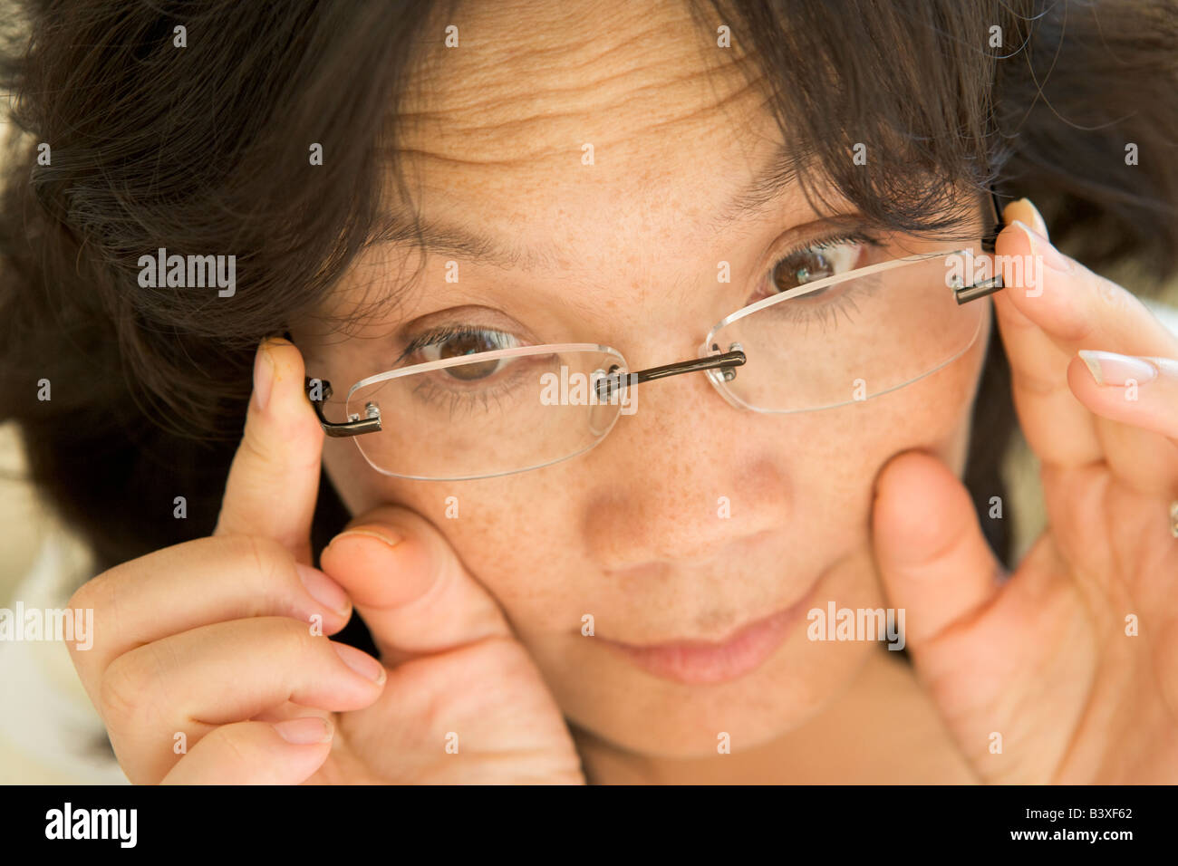 Woman Looking Through New Glasses - Stock Image