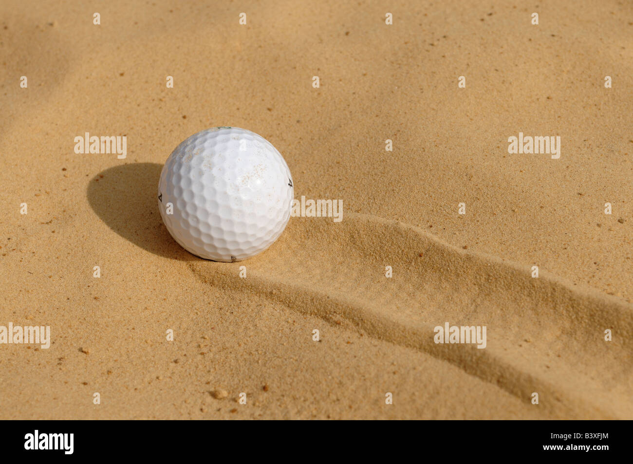 Golf ball in a bunker - Stock Image