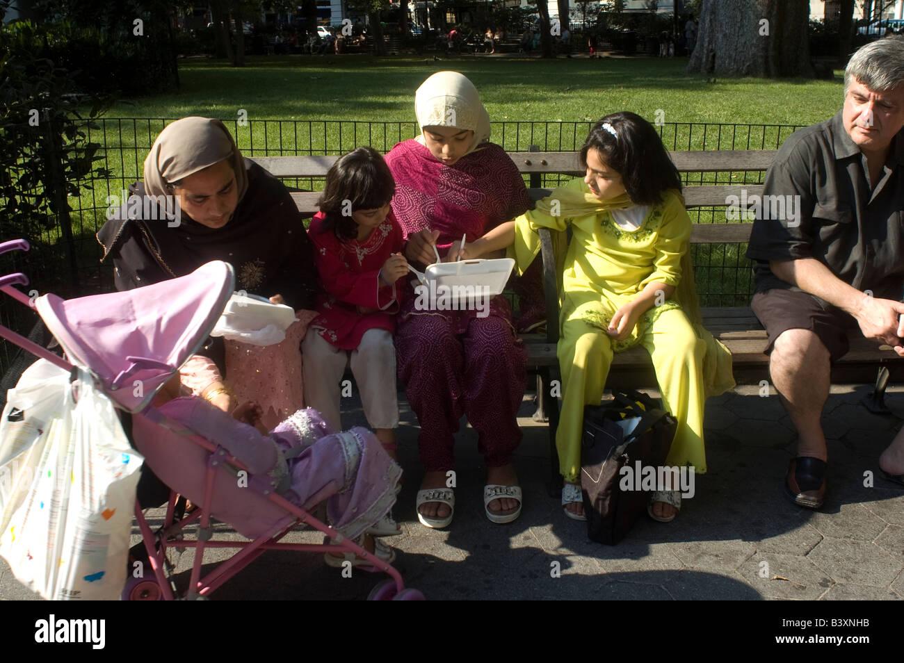 Pakistani women and young girls enjoy Pakistani snacks - Stock Image
