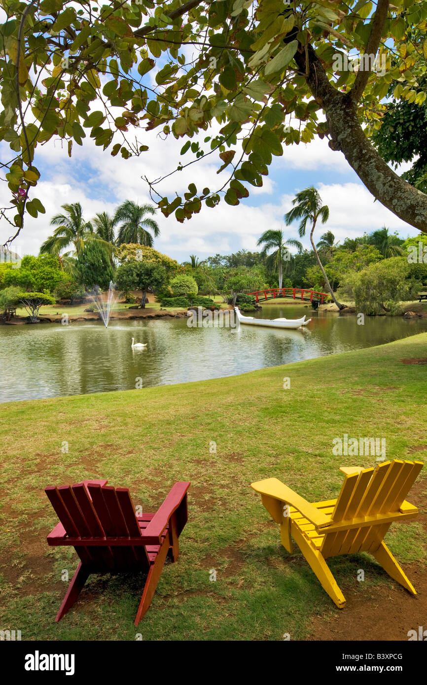 Two chairs overlooking boat and swan on pond at Smith s Tropical Gardens Kauai Hawaii - Stock Image