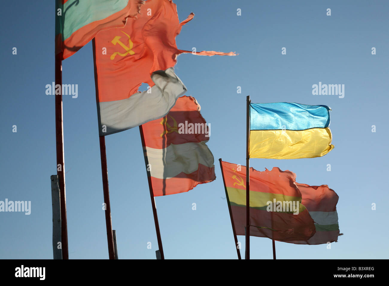 Old Soviet republics flags beside a modern Ukrainian flag waving over the pilgrim camp on the Solovetsky Islands, - Stock Image
