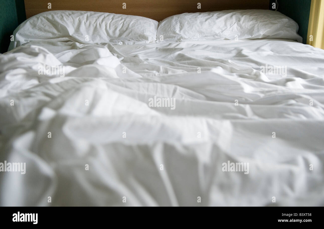 Unmade bed Bed sheets crumpled rumpled HOMER SYKES - Stock Image