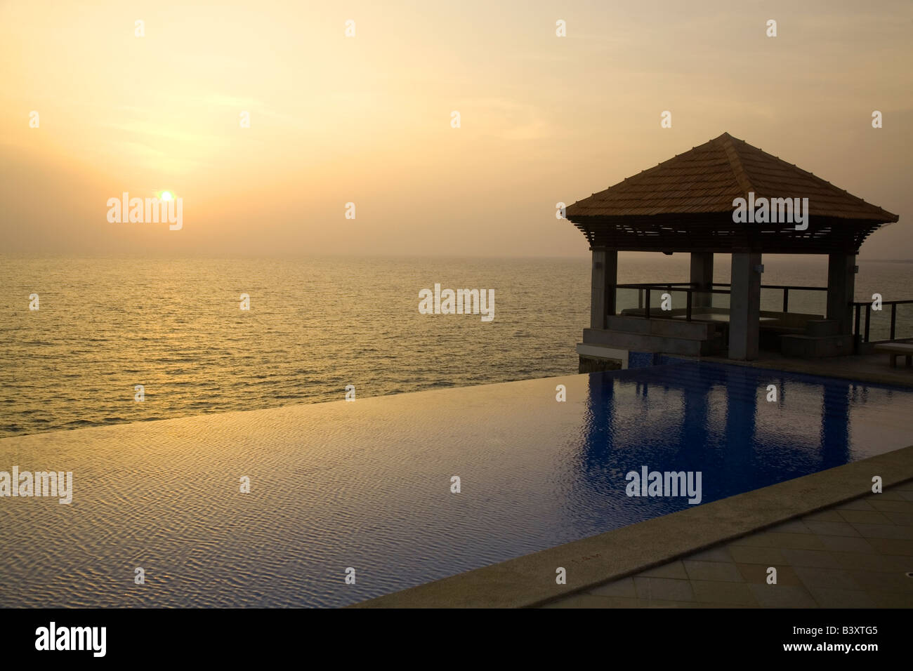 An infinity pool overlooks the Arabian Sea at Kovalam Beach in Kerala, India. Stock Photo