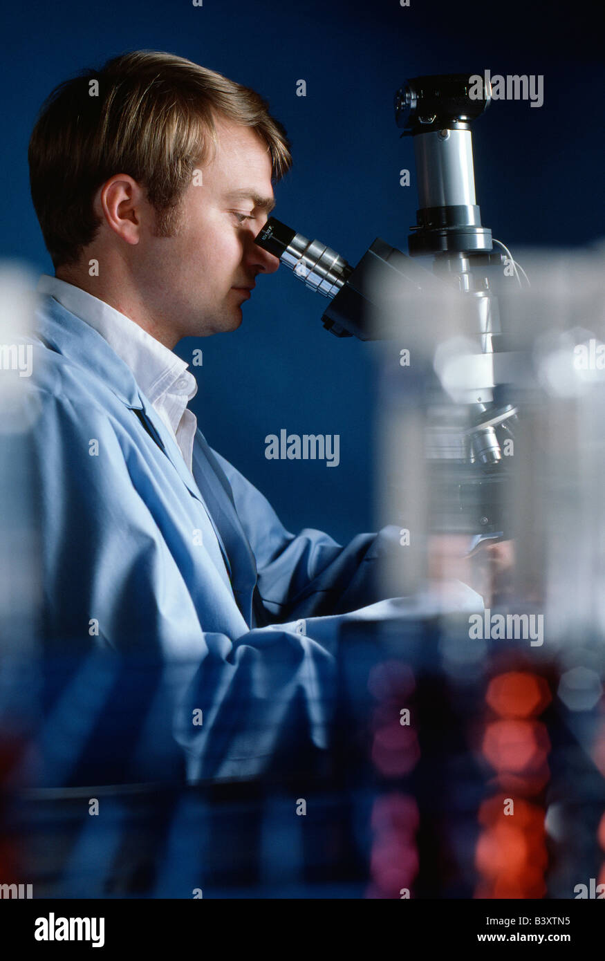 Technician checking water samples through a microscope in the quality control laboratory of a water treatment plant. Stock Photo