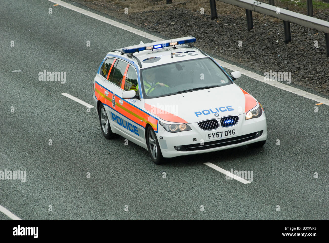 Bmw police car speeding along a motorway to an incident with blue flashing lights and siren on Stock Photo