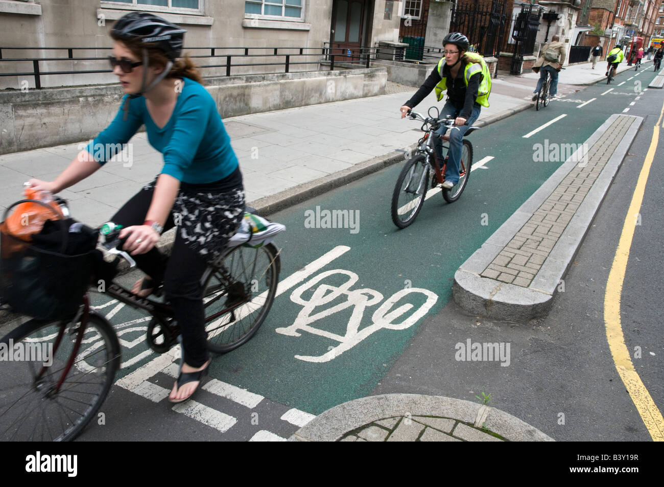 Cyclists riding in segregated cycling lane, London, England, UK - Stock Image