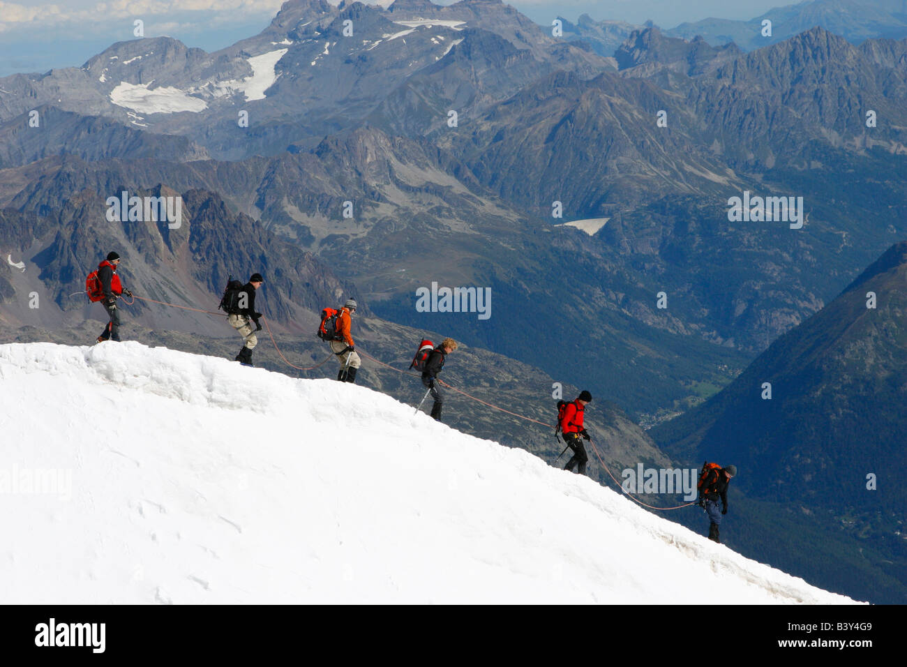 Mountaineers descend into the Vallee Blanche from the summit of the Aiguille du Midi cable car, Chamonix, French - Stock Image