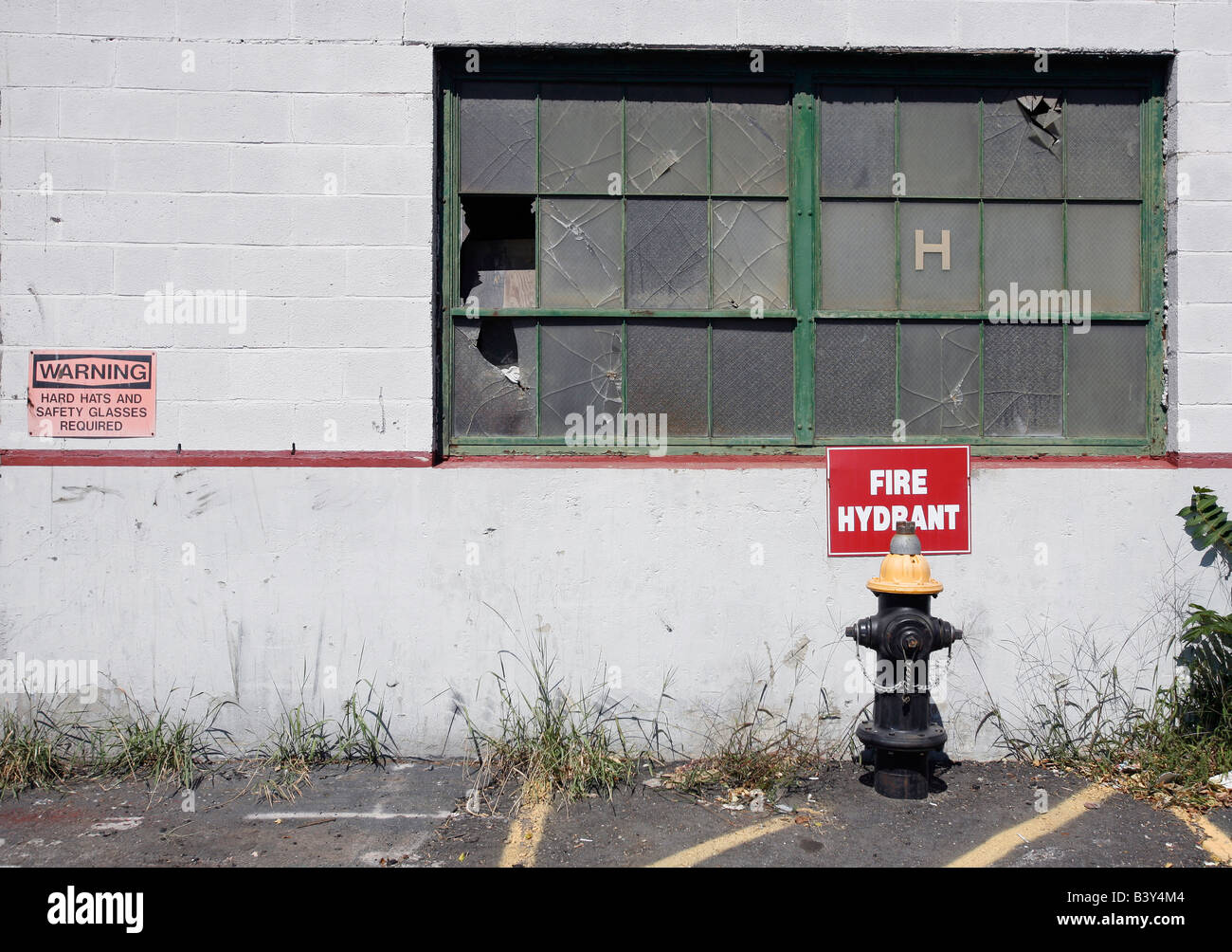 urban decay abandoned building weeds broken windows - Stock Image