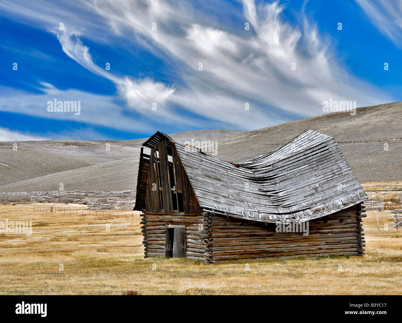 Fallen down barn with wispy clouds Montana - Stock Image