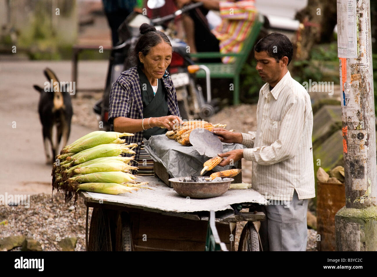 A woman buys sweet corn from a man in Dharamsala. Stock Photo