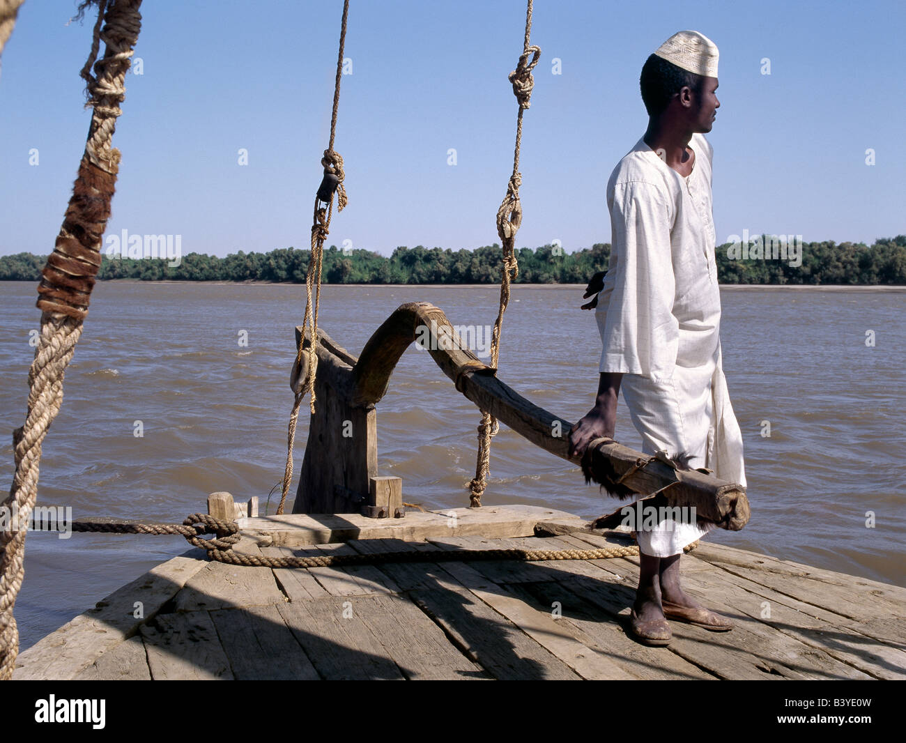 Sudan, Delgo. A Nubian boatman at the helm of his felucca, a wooden sailing boat that plies the waters of the River - Stock Image