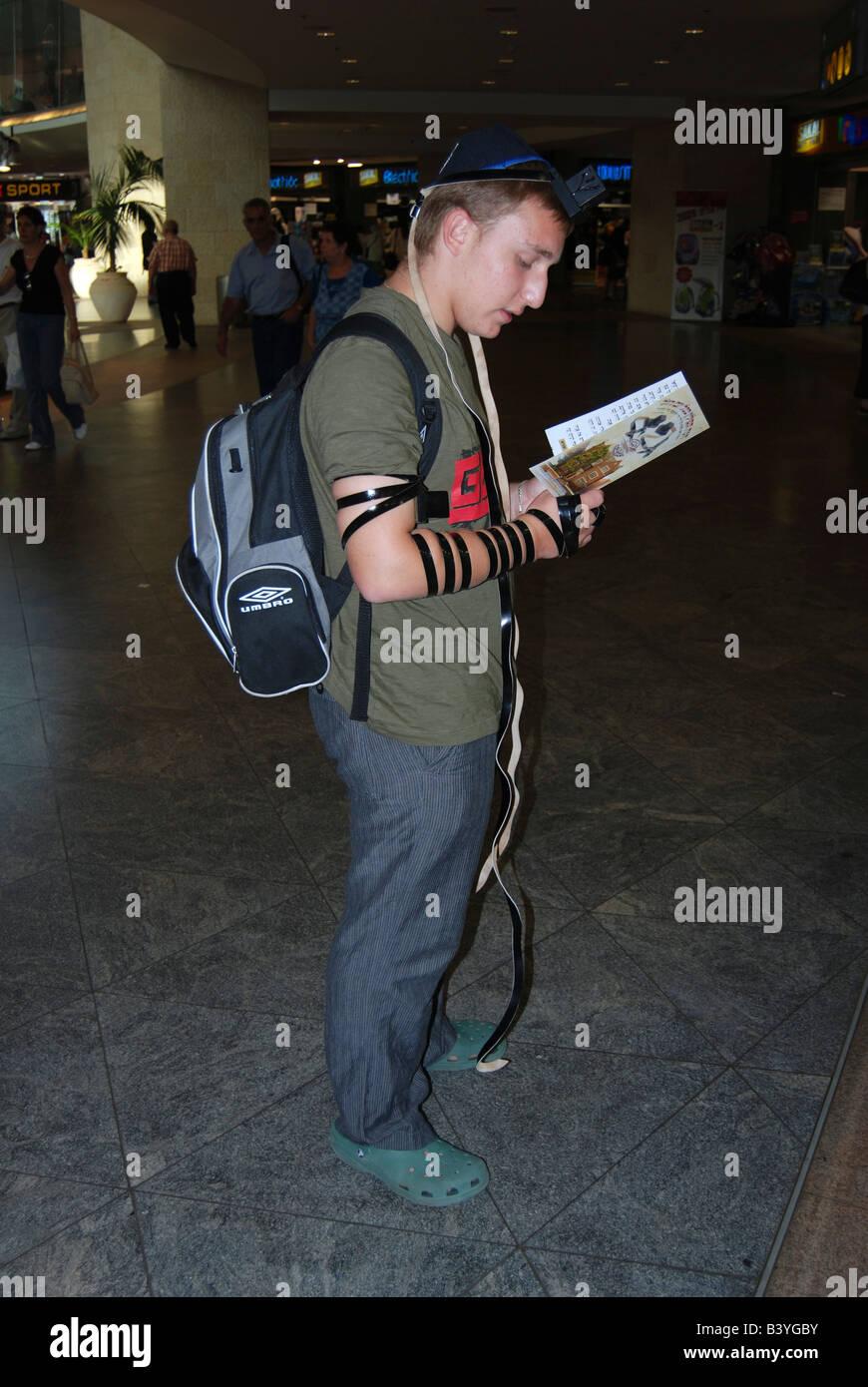 young Jewish man praying At Ben Gurion Airport Israel - Stock Image