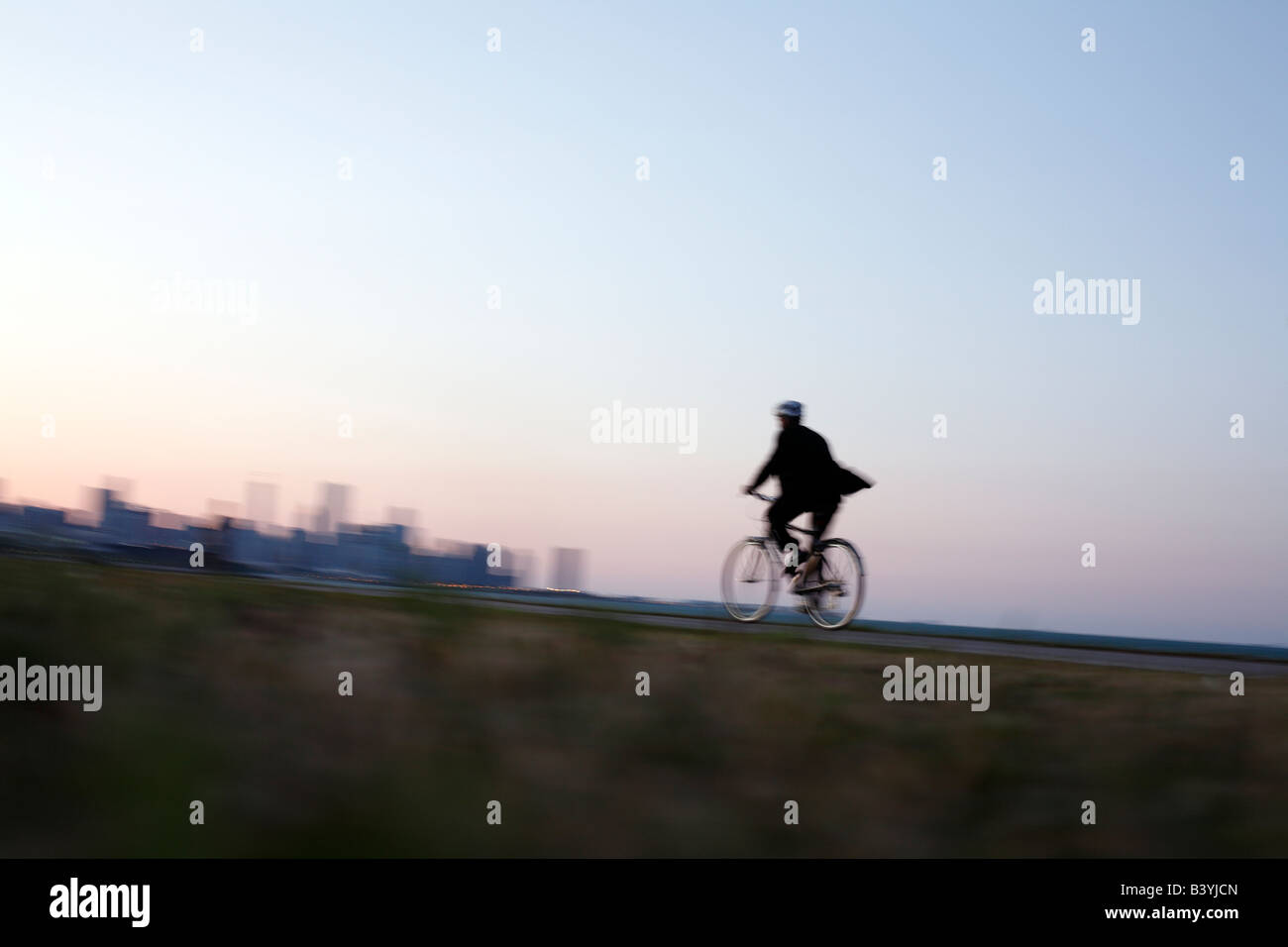 Man in suit rides bicycle along Chicago lakefront - Stock Image