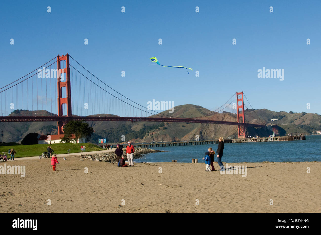 A family flies a kite at Crissy Field near the Golden Gate Bridge in San Francisco CA California - Stock Image