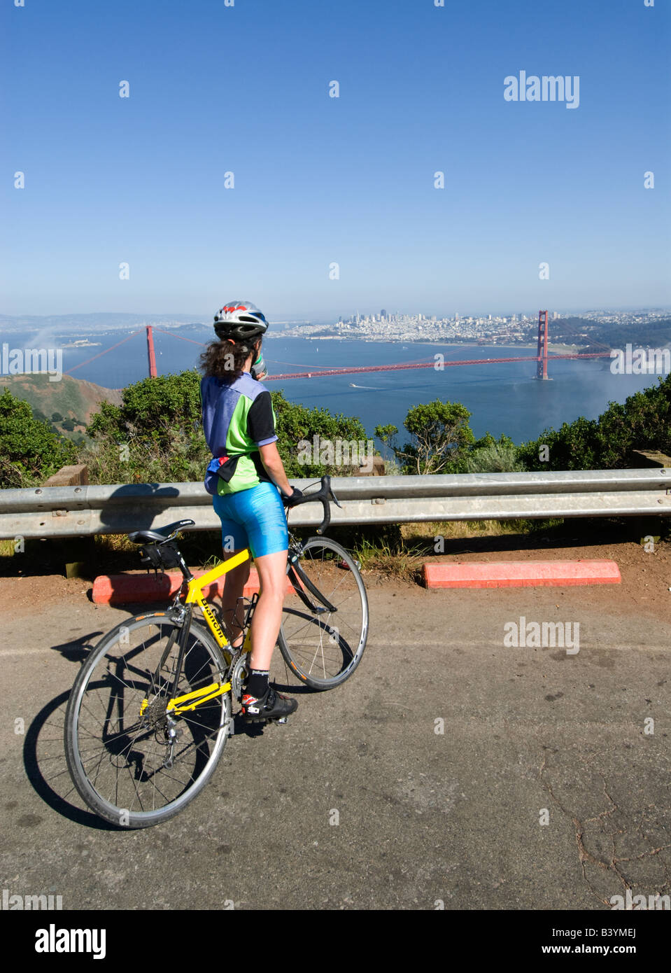 A woman bicyclist pauses at Hawk Hill in Marin County to admire the Golden Gate Bridge - Stock Image