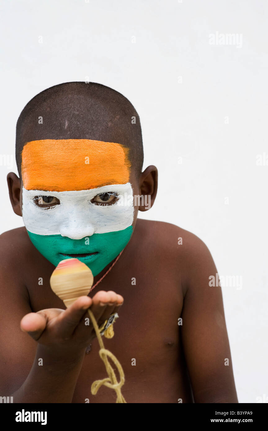 Indian boy with indian flag painted on his face playing with a