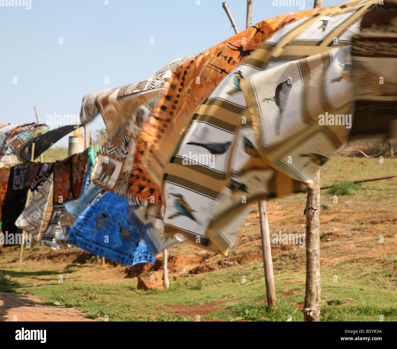 The colourful table cloths and wall hangings, made by local South African women, blowing in the wind on a clothes - Stock Image