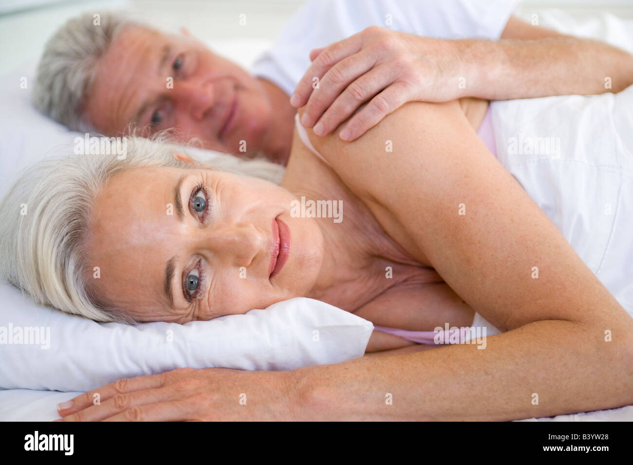 Couple lying in bed together smiling - Stock Image