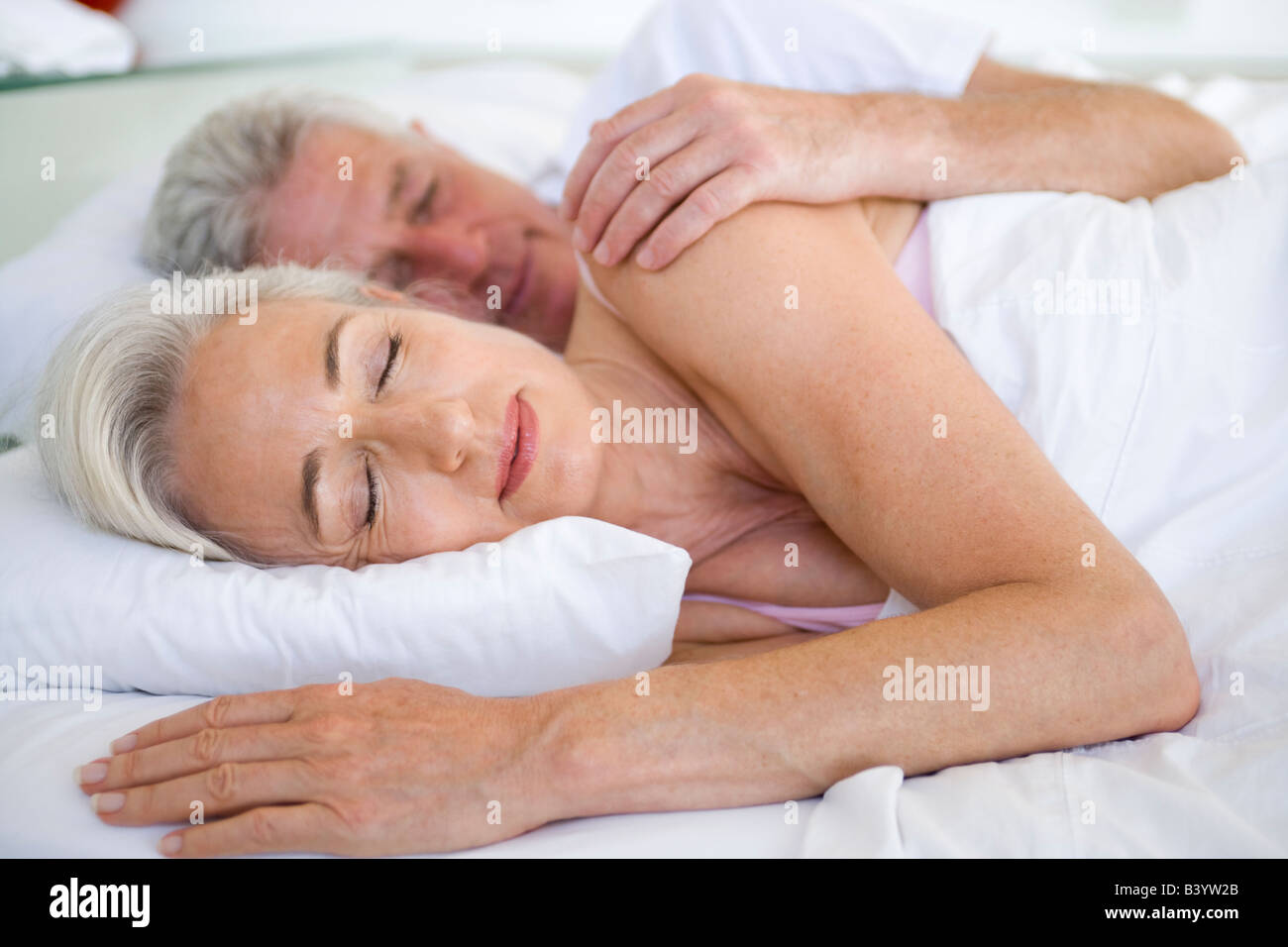 Couple lying in bed together sleeping - Stock Image
